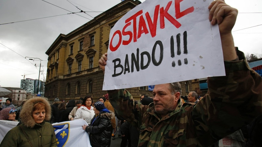 "Bosnian people march as one holds up a sign that reads "" resignation bandits !!! "" in the Bosnian capital of Sarajevo, Sunday, Feb. 9, 2014. More than 500 people gathered in Sarajevo demanding the resignation of the government and the release of people arrested on Friday during a protest. (AP Photo/Amel Emric)"