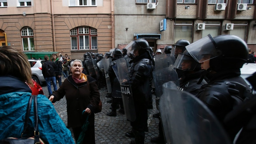 Bosnian woman protest in front of a police cordon in the Bosnian capital of Sarajevo, Sunday, Feb. 9, 2014. More than 500 people gathered in Sarajevo demanding the resignation of the government and the release of people arrested during a Friday protest. (AP Photo/Amel Emric)