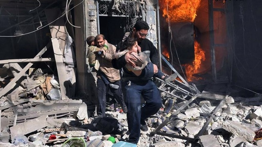 Feb. 8, 2014: In this photo provided by the anti-government activist group Aleppo Media Center (AMC), which has been authenticated based on its contents and other AP reporting, Syrian men help survivors out of a destroyed building after a Syrian forces warplane's attack in Aleppo, Syria.