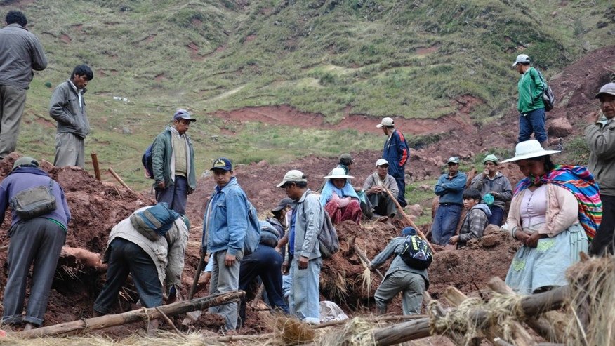 Farmers dig through the mud in search of survivors and recovery of bodies after a mudslide buried a small settlement in Chullpa Kasa, Bolivia, Sunday, Feb. 9, 2014. Local officials in Bolivia say that heavy rains have caused a mudslide, killing at least four people. Another nine people are missing. Heavy rains have been falling across most of Bolivia since November and an estimated 46,800 families have been affected. (AP Photo)