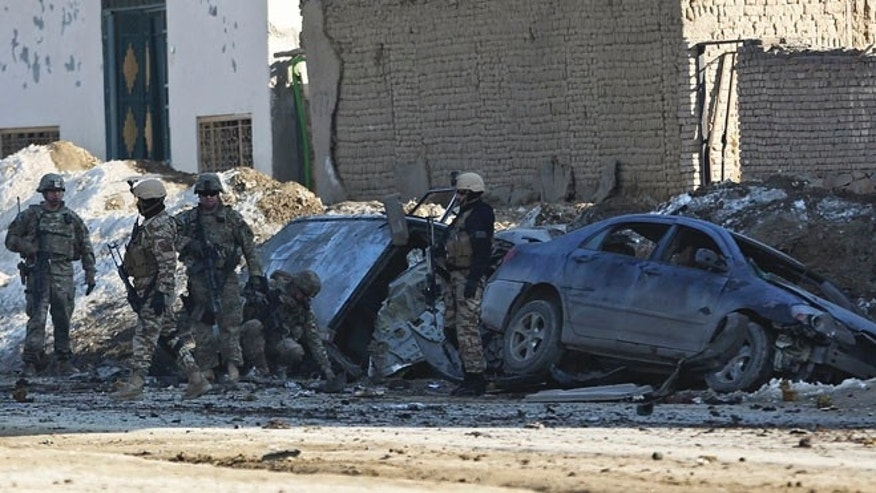 Feb. 10, 2014: U.S. soldiers and Afghan security forces search the site of a suicide bombing that struck near a NATO convoy in the Afghan capital Kabul, Afghanistan.