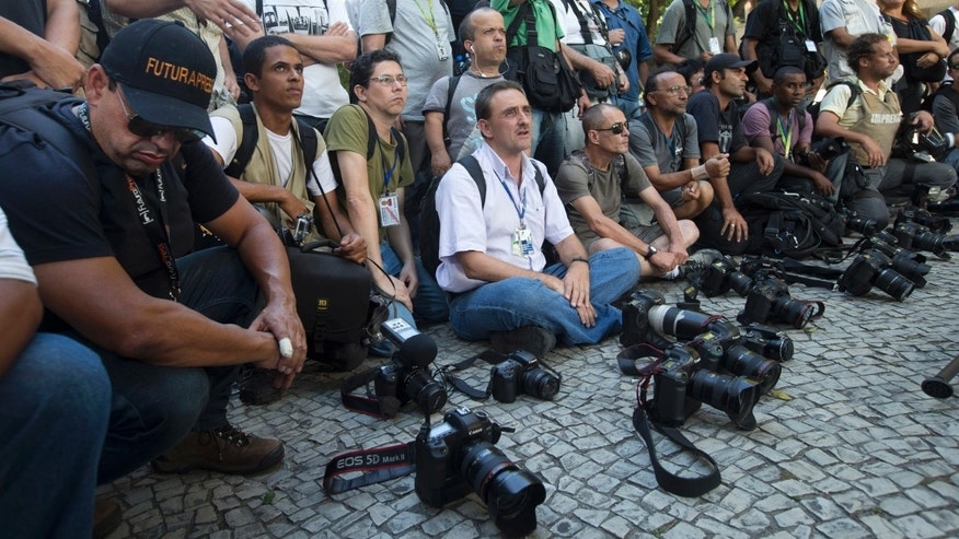 Journalist put their cameras down for one minute, to draw attention to the case of a cameraman who was gravely injured by a flare while covering a protest last week in Rio de Janeiro, Brazil, Monday, Feb. 10, 2014. Brazilian television station Band TV said in a Monday statement that 49-year-old journalist Santiago Andrade remains in a coma on life support, but that doctors have declared him brain dead. (AP Photo/Silvia Izquierdo)