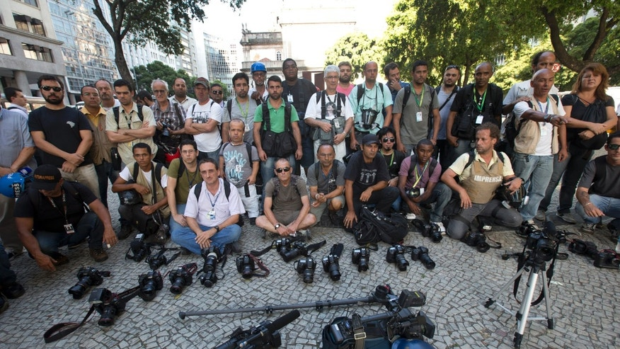 Journalist put their cameras down for one minute, to draw attention to the case of a cameraman who was gravely injured by a flare while covering a protest last week in Rio de Janeiro, Brazil, Monday, Feb. 10, 2014. Brazilian television station Band TV says in a Monday statement that 49-year-old journalist Santiago Andrade remains in a coma on life support, but that doctors have declared him brain dead.(AP Photo/Silvia Izquierdo)
