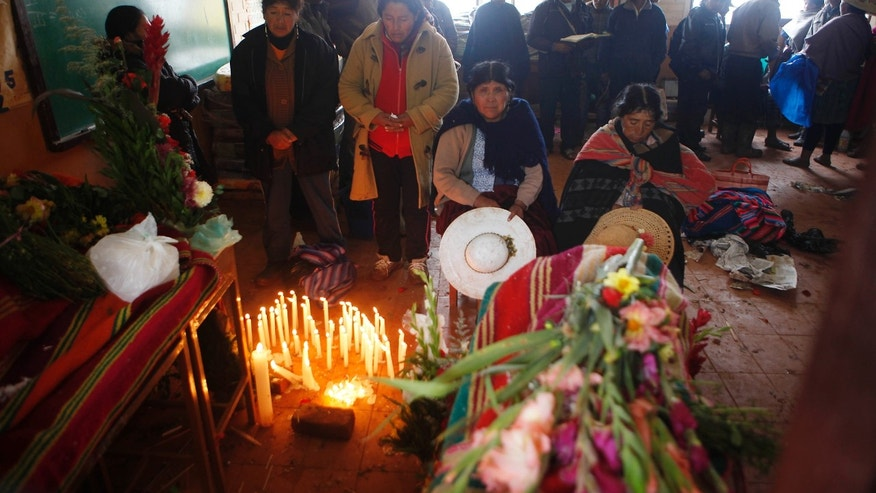People attend the wake for the persons killed by a mudslide in Chullpa Kasa, Bolivia, Monday, Feb.10, 2014. Heavy rains caused the mudslide that buried much of the small mountainside settlement in central Bolivia, killing at least four people, local officials said Sunday. Eleven more people were listed as missing on Monday. Heavy rains have been falling across most of Bolivia since November and civil defense officials say tens of thousands of families have been affected. (AP Photo/Juan Karita)