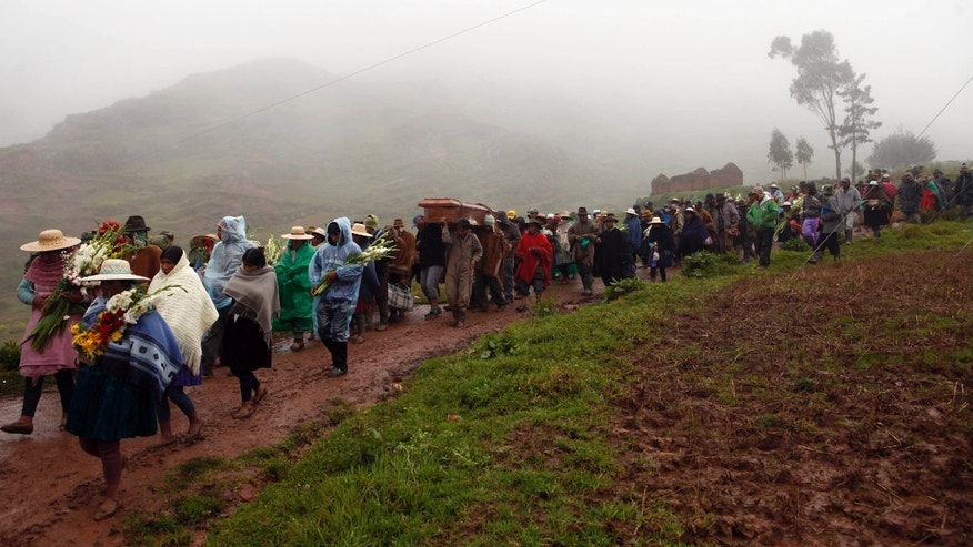 People carry the coffins towards the cemetery, of the persons killed by a mudslide in Chullpa Khasa, Bolivia, Monday, Feb.10, 2014. Heavy rains caused a mudslide that buried much of the small mountainside settlement in central Bolivia, killing at least four people, local officials said Sunday. Eleven more people were listed as missing on Monday. Heavy rains have been falling across most of Bolivia since November and civil defense officials say tens of thousands of families have been affected. (AP Photo/Juan Karita)