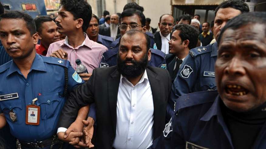 One of the two owners of Tazreen Fashions Ltd., Delwar Hossain, center, is escorted by security personnel to a court in Dhaka, Bangladesh, Sunday, Feb. 9, 2014. Two owners of a Bangladesh garment factory where 112 workers died in a fire two years ago surrendered on Sunday and sought bail after they were charged with homicide. (AP Photo)
