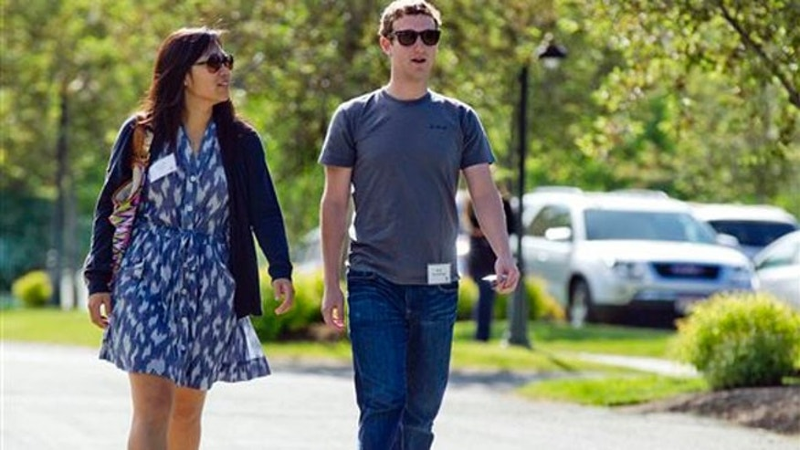 In this July 9, 2011, file photo, Mark Zuckerberg, president and CEO of Facebook, walks with Priscilla Chan during the 2011 Allen and Co. Sun Valley Conference, in Sun Valley, Idaho. Zuckerberg and his wife, Chan, were the most generous American philanthropists in 2013, The Chronicle of Philanthropy reported, Monday, Feb. 10, 2014, with a donation of 18 million Facebook shares, valued at more than $970 million, given to a Silicon Valley nonprofit in December. (AP)