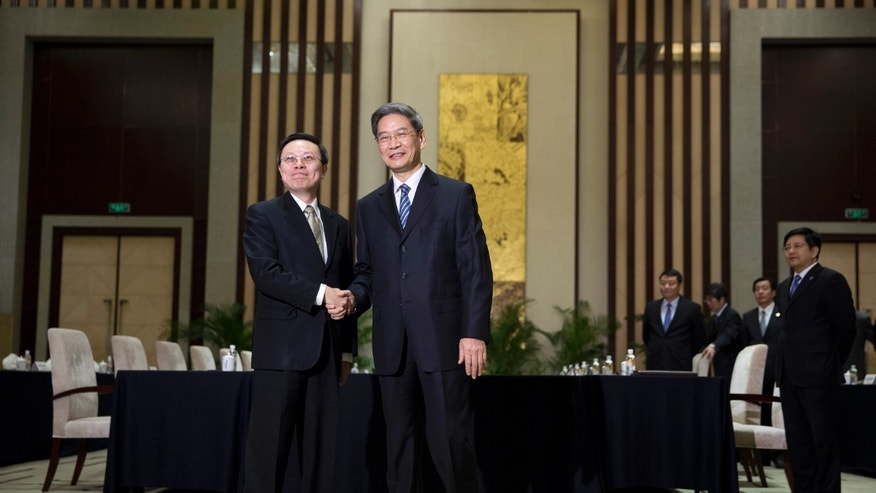 Wang Yu-chi, head of Taiwan's Mainland Affairs Council, left, and Zhang Zhijun, director of China's Taiwan Affairs Office, right, shake hands and pose for photos before their meeting in Nanjing, in eastern China's Jiangsu Province, Tuesday, Feb. 11, 2014. Taiwan and China are holding their highest-level talks since splitting amid a civil war 65 years ago, hoping to further boost contacts and ease lingering tensions, even as political developments on the self-governing island swing away from Beijing's goal of eventual unification. (AP Photo/Alexander F. Yuan)
