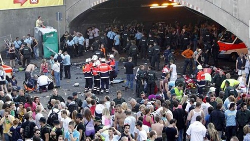 "FILE: July 24, 2010: Collapsed people get first aid after a panic on this year's techno-music festival ""Loveparade 2010"" in Duisburg, Germany."