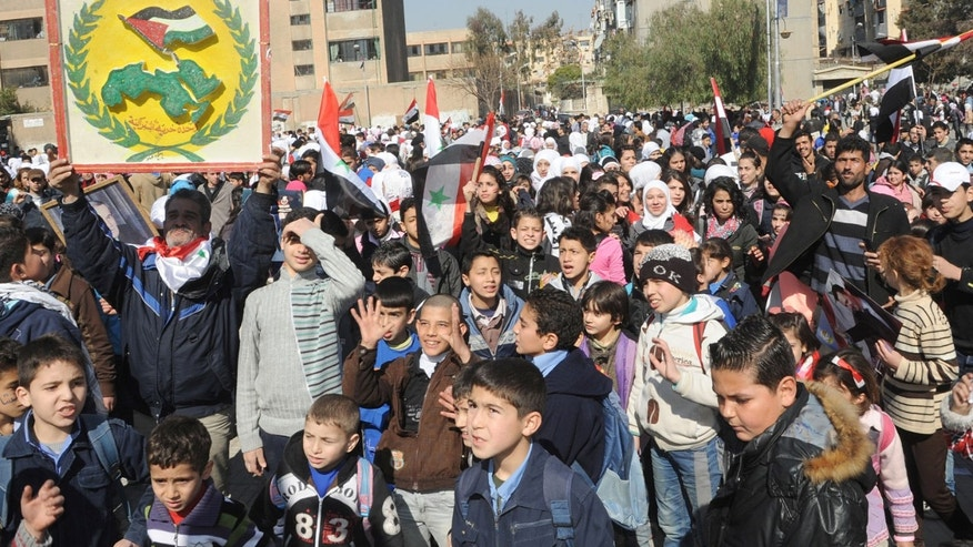 Feb. 11, 2014: In this photo released by the Syrian official news agency SANA, supporters of Syrian President Bashar Assad, wave Syrian flags and one holds up the logo of the Syrian Baath Party, left, as they march during a demonstration is solidarity with government forces, in the al-Midan neighborhood, of Damascus, Syria.