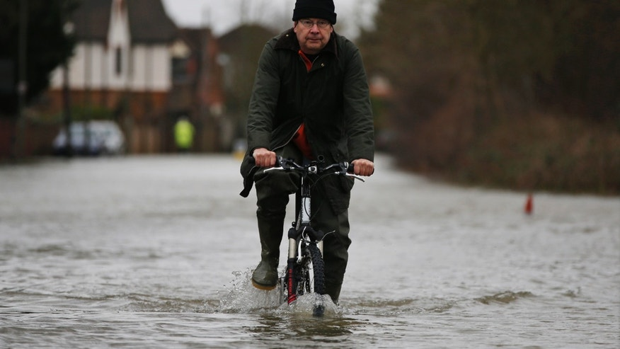 "A local resident cycles through the flooded part of the town of Staines-upon-Thames, England, Wednesday, Feb. 12, 2014. Prime Minister DavidCameron insisted Tuesday that money is no object in the battle against the widespread flooding that has engulfed parts of England. Canceling a visit to the Middle East to oversee flood-fighting efforts, he told journalists that ""whatever money is needed for this relief effort will be spent"" as Britain deals with some of its wettest weather in 250 years. (AP Photo/Lefteris Pitarakis)"