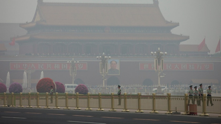 FILE - In this June 2, 2013 file photo, paramilitary policemen patrol on Tiananmen Square on a polluted day in Beijing, China. China's Cabinet has announced that 10 billion yuan ($1.6 billion) has been set aside this year to reward cities and regions that make significant progress in controlling air pollution, highlighting how the issue has become a priority for the leadership. (AP Photo/Alexander F. Yuan, File)