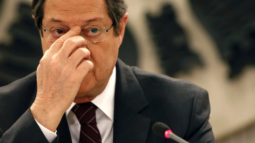 Cyprus's President Nicos Anastasiades adjusts his glasses before speaking during a national televised news conference at the Presidential Palace in Nicosia, Cyprus,  Wednesday, Feb. 12, 2014. Anastasiades held the conference to defend a document he agreed with Turkish Cypriot leader Dervis Eroglu that paved the way for the resumption of negotiations a day earlier aimed at reunifying the war-divided island. Anastasiades faces strong pressure from critics who argue that the document contains the seeds of possible Turkish Cypriot statehood, which could unravel any peace accord. (AP Photo/Petros Karadjias)