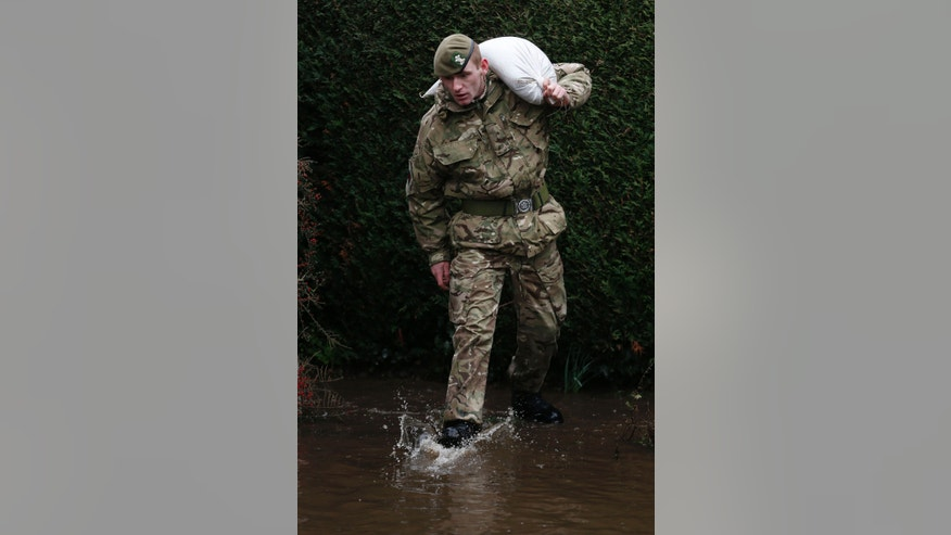 British army soldier carries a sand bag as troops work to help protect homes from rising flood waters at Chertsey, England, Wednesday, Feb. 12, 2014.  The River Thames has burst its banks after reaching its highest level for many years, flooding riverside towns upstream of London, including Chertsey which is about 30 miles west of central London. Some hundreds of troops have been deployed to assist with flood protection and to get medical assistance to the sick and vulnerable.(AP Photo/Sang Tan)