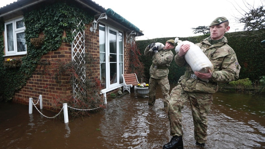 British army soldiers carry sandbags at the entrance to a flooded house at Chertsey, England, Wednesday, Feb. 12, 2014.  The River Thames has burst its banks after reaching its highest level for many years, flooding riverside towns upstream of London, including Chertsey which is about 30 miles west of central London. Some hundreds of troops have been deployed to assist with flood protection and to get medical assistance to the sick and vulnerable.(AP Photo/Sang Tan)