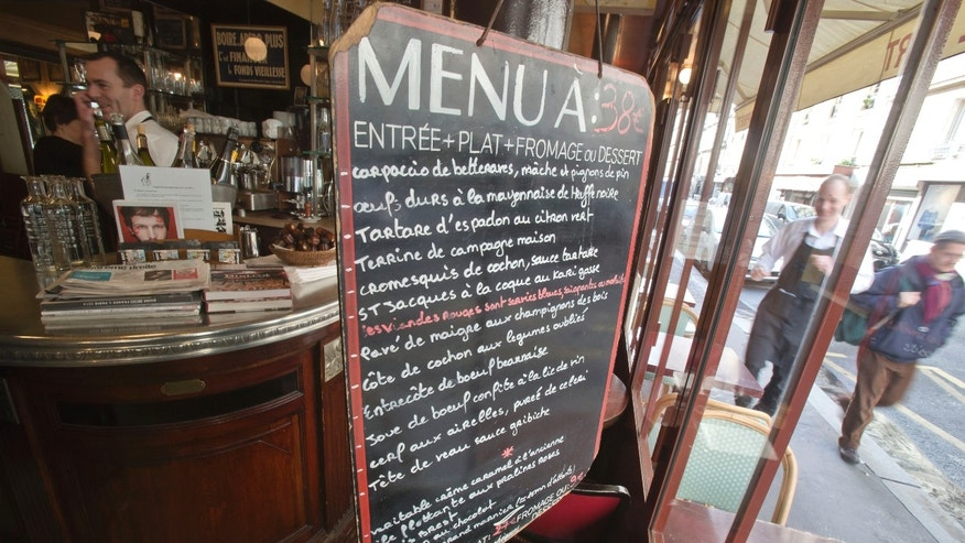 "The menu is seen at the entrance of the Bistro Paul Bert in the trendy 11th arrondissement of Paris, Wednesday, Feb. 12, 2014. Thierry Laurent, chef at Paul Bert for 14 years, is proud to cook each dish in the purest French tradition.  Waiting for boeuf bourguignon in a charming French bistro, it's hard to imagine that the chef's main job could be to press buttons on the microwave. But frozen and pre-packaged meals have become so common in restaurants that lawmakers want customers to know what they're getting.  A new law, to be voted Thursday, would let restaurants label a dish ""fait maison"" _ homemade _ only when it's made in-house from fresh ingredients. Supporters say the law could create jobs by encouraging a return to traditional restaurant cooking. (AP Photo/Michel Euler)"