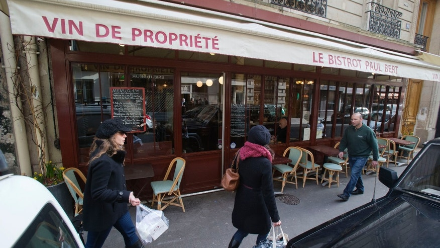 "People walk past of the Bistro Paul Bert in the trendy 11th arrondissement of Paris, Wednesday, Feb. 12, 2014.  Thierry Laurent, chef at Paul Bert for 14 years, is proud to cook each dish in the purest French tradition.  Waiting for boeuf bourguignon in a charming French bistro, it's hard to imagine that the chef's main job could be to press buttons on the microwave. But frozen and pre-packaged meals have become so common in restaurants that lawmakers want customers to know what they're getting.  A new law, to be voted Thursday, would let restaurants label a dish ""fait maison"" _ homemade _ only when it's made in-house from fresh ingredients. Supporters say the law could create jobs by encouraging a return to traditional restaurant cooking.  (AP Photo/Michel Euler)"
