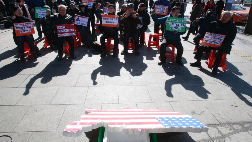 "Protesters stage a rally opposing the scheduled visit of Secretary of State John Kerry near the U.S. embassy in Seoul, South Korea, Tuesday, Feb. 11, 2014. Kerry will visit  South Korea on Thursday to discuss issues of mutual concerns, including efforts to denuclearize North Korea. The letters at cards read "" Oppose South Korea and U.S. joint military exercise and scrap the South Korea-U.S. alliance"". (AP Photo/Ahn Young-joon)"