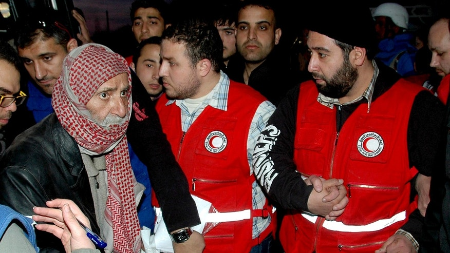 In this photo taken on Monday Feb. 10, 2014, and released by the Syrian official news agency SANA, Syrian Arab Red Crescent members in red uniforms help an elderly man on to a bus to evacuate the battleground city of Homs, Syria. The Syrian government has allowed 111 men of fighting age to leave rebel-held areas of the besieged city of Homs after they were questioned and cleared of rebel links. (AP Photo/SANA)
