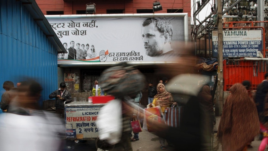 In this Feb. 8, 2014 photo, Indian people walk past a Congress party hoarding displaying portrait of their vice president Rahul Gandhi, right, and party symbol in old quarters of New Delhi, India. Election season in India always comes with heaps of promises, as political parties try to woo voters with everything from subsidized fuel and electricity to free laptops, spice grinders, even goats and cows.  But there are growing concerns that freebies will hurt the country's sputtering economy. (AP Photo/Tsering Topgyal)
