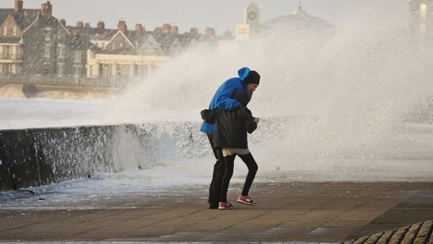 People struggle to make their way along the Esplanade, Porthcawl, south Wales, as the region continues to be battered by high winds and heavy rain.