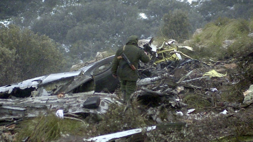 A man walks through the wreckage of an Algerian military transport plane which slammed into a mountain Tuesday,  in the country's rugged eastern region, Wednesday, Feb. 12, 2014. The crash killed scores of people and left just one survivor, the defense ministry said. The plane was discovered in pieces on Mount Fortas near the town of Ain Kercha, 50 kilometers (30 miles) southeast of Constantine, the main city in eastern Algeria. (AP Photo/Anis Belghoul)