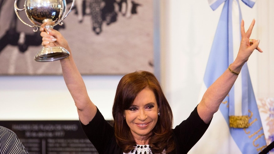 Argentine President Cristina Fernandez lifts a trophy given to her by a supporter during an event at the Casa Rosada government palace in Buenos Aires, Argentina,  Wednesday, Feb. 12, 2014. The trophy had been given to the supporter by the late Argentine President Juan Domingo Peron for winning a chess tournament . (AP Photo/Victor R. Caivano)