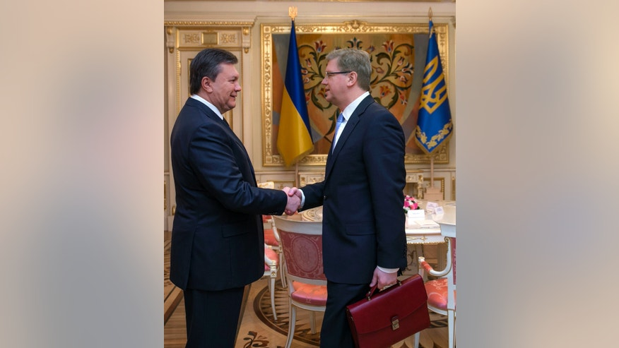 Ukrainian President Viktor Yanukovych, left, greets European Commissioner for Enlargement and European Neighborhood Policy Stefan Fule in Kiev, Ukraine, Wednesday, Feb. 12, 2014. (AP Photo/Andrei Mosienko, Pool)