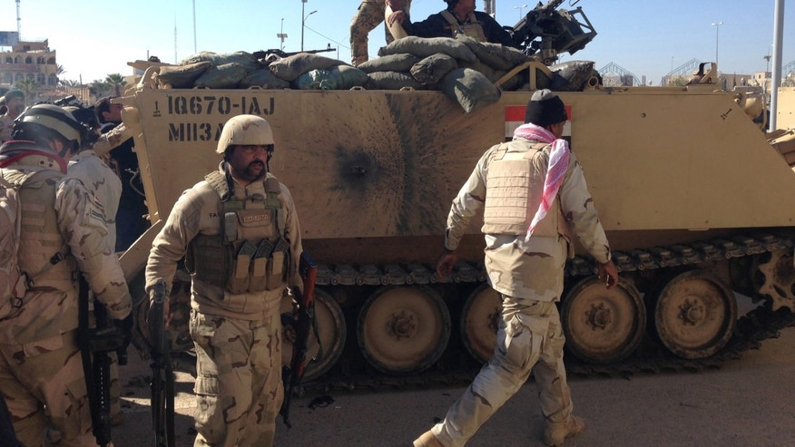 FILE - In this Saturday, Feb. 1, 2014, file photo, Iraqi army soldiers inspect their armored vehicle after it was hit during clashes in Ramadi, Iraq. More than a month after jihadist militants seized control of parts of Iraq's western Anbar province, an unsettling realization is sinking in: Iraq's government could face a tougher time beating back an insurgency there than the hard slog the Americans faced last decade. The reasons include a deep distrust of the government by Iraqi Sunnis, insufficient resources, sectarian tensions enflamed by the war in Syria and divisions among the tribes that make up Anbar's social fabric. (AP Photo, File)