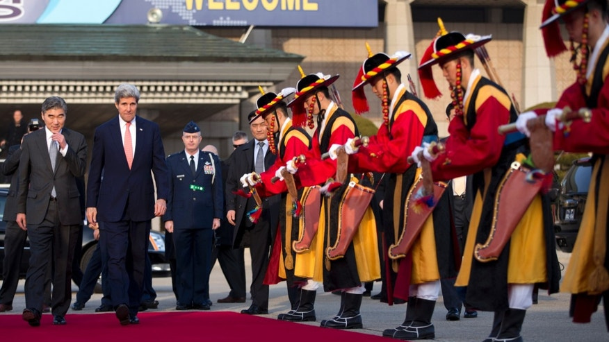 U.S. Secretary of State John Kerry, second left, walks to his plane to depart on a flight to Beijing on Friday, Feb. 14, 2014, in Seoul, South Korea. Kerry is visiting South Korea, China, Indonesia, and the United Arab Emirates on a seven-day trip. (AP Photo/Evan Vucci, Pool)