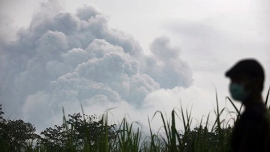 Feb. 14, 2014: A man watches from Mbaladak village in Blitar, East Java, Indonesia, as Mount Kelud erupts.
