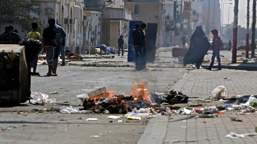 Bahraini anti-government protesters watch for riot police between clashes in the debris-filled main street of Malkiya, Bahrain, Thursday, Feb. 13, 2014. Rubbish and oil smeared on the road are meant to deter police jeeps from entering the village, where shops were shuttered in observance of a general strike called by anti-government groups in the run-up to Friday's third anniversary of the pro-democracy uprising in the Gulf island kingdom. (AP Photo/Hasan Jamali)