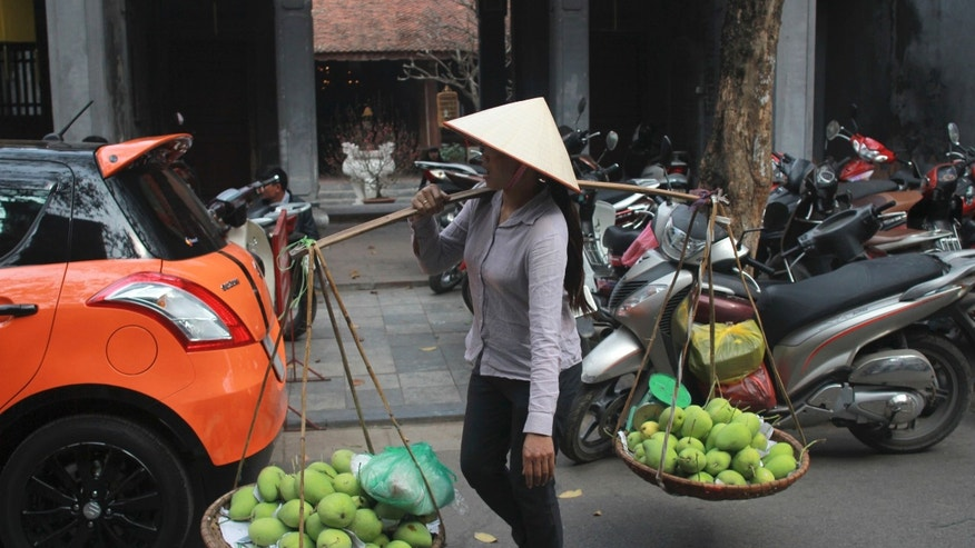 In this Jan. 27, 2014 photo, a street vendor walks by Kim Ngan Temple on Silver Street in the Old Quarter of Hanoi, Vietnam. The 82-hectare (203-acre) area is crammed with Buddhist temples, pagodas and French-colonial shophouses, whose original tiles and peeling yellow paint have become a draw for foreign visitors. It is now among Asia's best-preserved urban hubs of traditional commerce - thanks largely to decades of inattention. (AP Photo/Mike Ives)