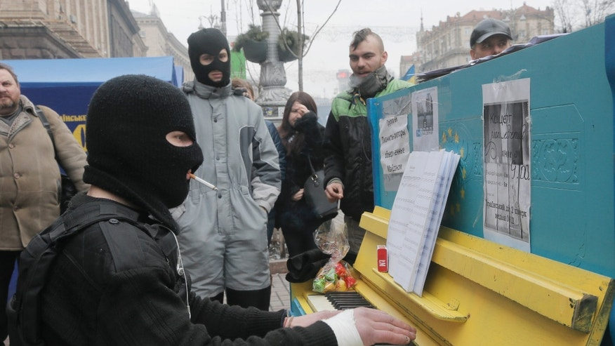 A protester in a balaclava and a flak jacket plays the piano in Kiev's Independence Square, the epicenter of the country's current unrest, Ukraine, Friday, Feb. 14, 2014. A Ukrainian opposition group says that all the protesters detained during nearly three months of opposition demonstrations have been released under an amnesty law. (AP Photo/Efrem Lukatsky)