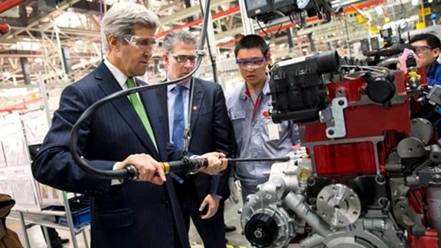 Feb. 15, 2014: Secretary of State John Kerry, left, torques an engine bolt during a tour of the Foton Cummins Engine plant in Beijing, China. Kerry toured the plant and made remarks on climate change cooperation between the United States and China.