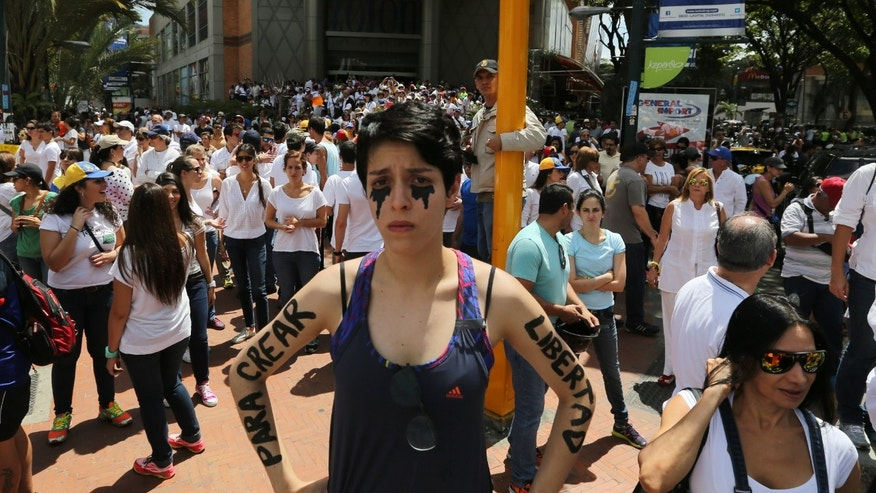 "An opposition protester stands in silence with her arms painted with the words in Spanish ""To create freedom"" during a protest in Caracas, Venezuela, Saturday, Feb. 15, 2014. Demonstrators are protesting the Wednesday killings of two university students who were shot in different incidents after an anti-government protest demanding the release of student protesters arrested in various parts of the country. (AP Photo/Fernando Llano)"