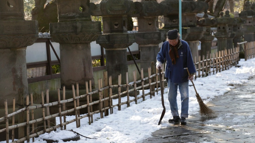 A worker walks away after shoveling snow off a court yard at a temple in Tokyo, Sunday, Feb. 16, 2014. (AP Photo/Shizuo Kambayashi)