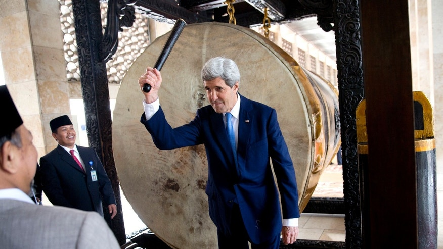 U.S. Secretary of State John Kerry raises his hand after beating the call to prayer drum during a tour of the Istiqlal Mosque with Grand Imam K.H. Ali Mustafa Yaqub, left, on Sunday, Feb. 16, 2014, in Jakarta. The Istiqlal Mosque is the largest mosque in Southeast Asia, capable of holding 120,000 people, and is the National Mosque of Indonesia. (AP Photo/ Evan Vucci, Pool)
