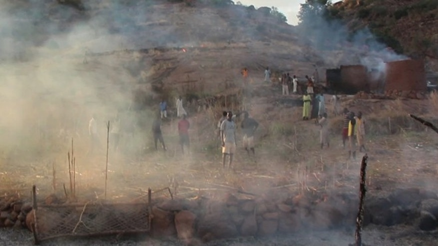 Villagers in the Nuba Mountains region look at the aftermath of a parachute bomb attack from Sudanese forces.