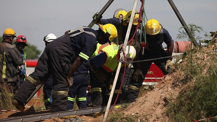 Feb. 16, 2014: Emergency rescue workers attempt to free trapped illegal miners at a disused gold mine shaft near, Benoni, South Africa.