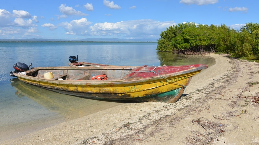 In this Jan. 25, 2014 photo, a fishing boat rests on a sandy beach of uninhabited Little Goat Island, Jamaica. The island is one of two outlying cays fringed by mangroves located less than a mile off the southern Jamaican town of Old Harbor. A skirmish has been brewing between the Jamaican government and the conservation lobby over a transshipment port to be developed by state-run China Harbor Engineering Co. that is planned for the uninhabited Goat Islands in a swath of the island's biggest protected area. (AP Photo/David McFadden)
