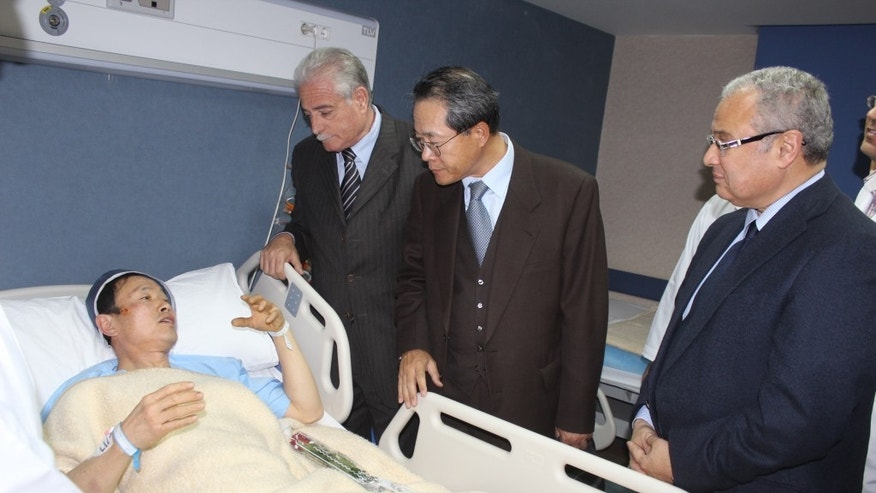 In this photo released by the office of the South Sinai governor, Egyptian Minister of Tourism Hesham Zazou, right, Deputy Chief of Mission of the South Korean Embassy in Egypt, Mr. Kwon Sae Young, second right, and South Sinai governor Major General Khaled Foda, visit a South Korean tourist who was injured during an explosion that targeted a tourist bus, as he received medical treatment in Sharm El-Sheik hospital, in Egypt, late Sunday, Feb. 16, 2014. An explosion ripped through a tourist bus near a border crossing between Egypt and Israel in the Sinai Peninsula, killing several South Koreans and the Egyptian driver, security officials said. (AP Photo/Office of the South Sinai governor)