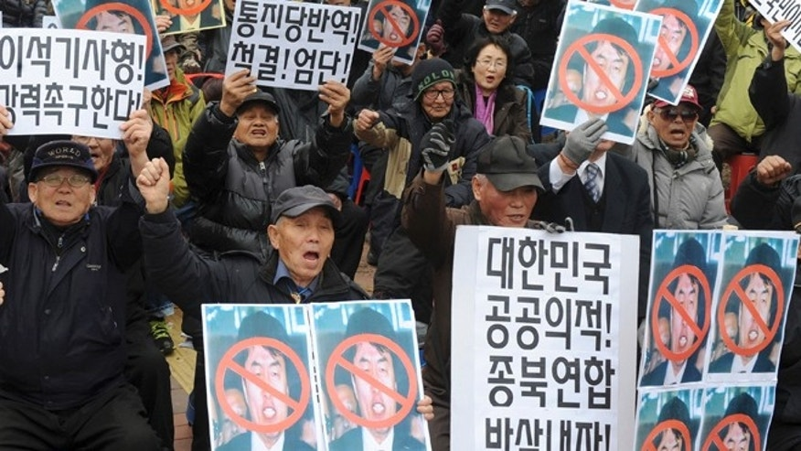 "Feb. 17, 2014: Conservative activists hold defaced photos of leftwing lawmaker Lee Seok-ki of the Unified Progressive Party while shouting slogans during a rally against Lee in front of the Suwon District Court in Suwon, South Korea. The court on Monday sentenced Lee to 12 years in prison for plotting a pro-North Korea rebellion in the event of a war on the Korean Peninsula. The placards held by the protesters read: ""Lee Seok-ki's rebellion, strongly demand execution."""