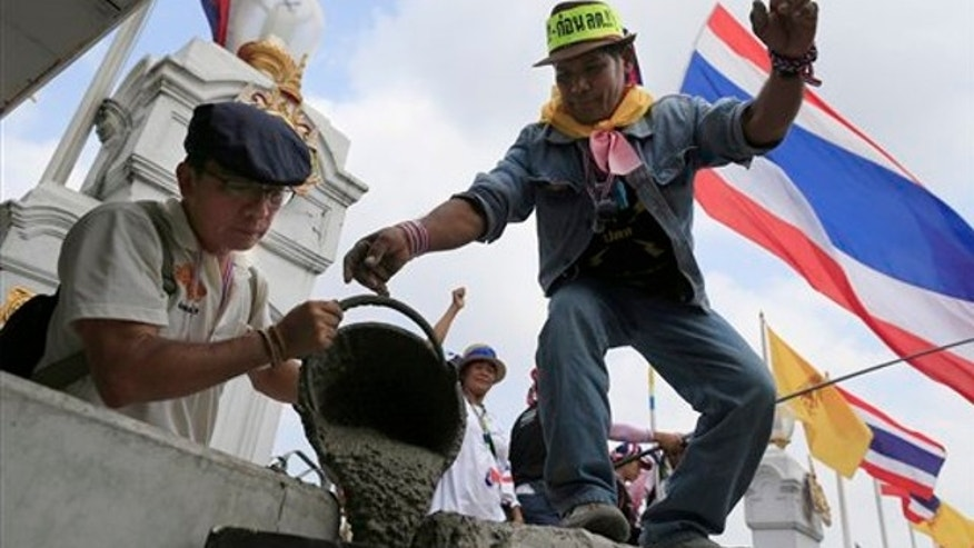 Feb. 17, 2014: Anti-government protesters pour cement on concrete barriers to seal the gate of the prime minister's office of government house during a rally in Bangkok, Thailand.