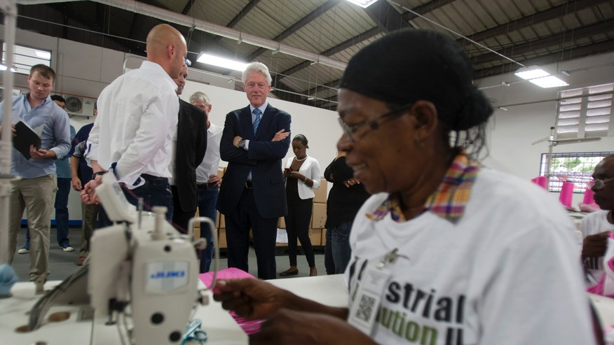 Former U.S. President Bill Clinton observes a worker at the new apparel manufacturer, Industrial Revolution II, S.A. in Port-au-Prince, Haiti, Tuesday Feb. 18, 2014. The manufacturer plans to reinvest half its profits into a health care and education program. Clinton is in a two-day trip to Haiti to visit several projects that focus on agriculture and the environment. (AP Photo/Dieu Nalio Chery)