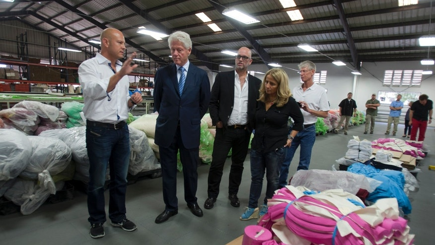 Former U.S. President Bill Clinton listens to Rob Broggi, left, CEO of Industrial Revolution during his visit to the apparel manufacturer's plant in Port-au-Prince, Haiti, Tuesday Feb. 18, 2014. Clinton visited the manufacturer, which plans to reinvest half its profits into a health care and education program. The former U.S. president is in a two-day trip to Haiti to visit several projects that focus on agriculture and the environment. (AP Photo/Dieu Nalio Chery)