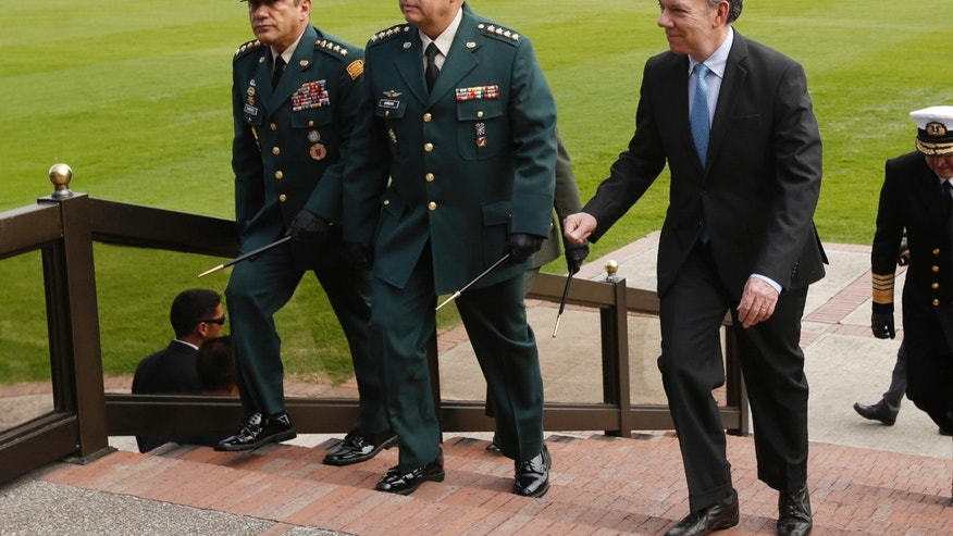 In this photo taken on Thursday, Feb. 13, 2014, Colombia's President Juan Manuel Santos, right, Colombia's armed forces chief Gen. Leonardo Barrero, center, and army commander Gen. Juan Pablo Rodriguez, left, attend a military ceremony in Bogota, Colombia. Santos announced that changes on the military chain of command will be decided Tuesday, Feb. 18, 2014, after the country's leading newsmagazine, Semana, reported on what it called widespread kickbacks in multimillion-dollar military contracts, and the publication online of an audio recording in which Gen. Leonardo Barrero is heard verbally maligning prosecutors' investigations into the extrajudicial killings that have brought Colombia international reproach. (AP Photo/Fernando Vergara)