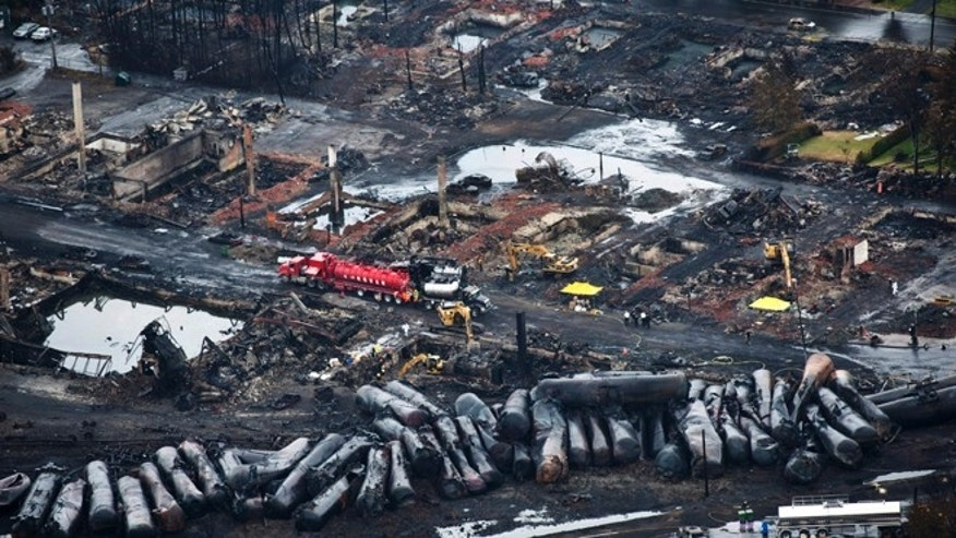 July 9, 2013: In this file photo, workers comb through debris after an oil train derailed and exploded in the town of Lac-Megantic, Quebec, killing 47 people. In response to Lac-Megantic, the National Transportation Safety Board and Transportation Safety Board of Canada in January 2014, called on regulators to require railroads to take stock of the risks along certain oil train routes and change them if needed.