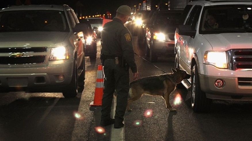 NOGALES, AZ - DECEMBER 07:  A border patrol agent and Gitta, a drug-sniffing German shepherd, work a checkpoint on December 7, 2010 north of Nogales, Arizona. The checkpoint falls in the Tucson sector of the U.S.- Mexico border and is considered the most heavily trafficked by illegal immigrants and drug smugglers in the United States.  (Photo by John Moore/Getty Images)