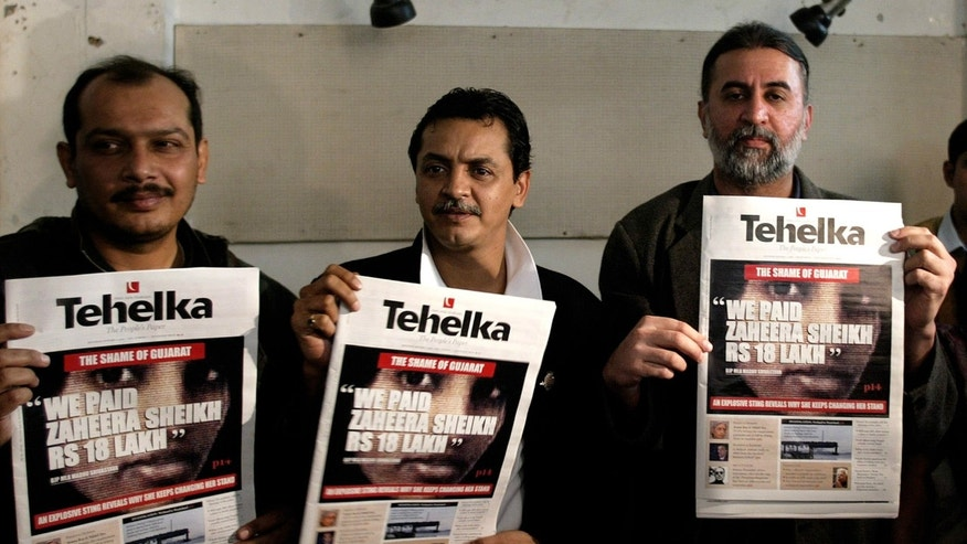 FILE - In this Dec. 22, 2004 file photo, Tehelka Editor Tarun Tejpal, right, his colleagues Sankarshan Thakur, center, and Amit Sengupta hold copies of the Tehelka paper in which the newspaper claims to have exposed that Zahira Sheikh, key witness in the 2002 Gujarat riots, was paid money for turning hostile, during a press conference in New Delhi, India. Police filed rape and sexual abuse charges against Tejpal, editor of an Indian magazine known for exposing abuses of power Monday, Feb. 17, 2014. Police also noted on Monday's charge sheet that Tejpal had tried to evade arrest after being accused by a young female colleague of sexually assaulting her in a hotel elevator during a conference in early November. (AP Photo/Manish Swarup, File)
